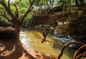 Sob calor de quase 40ºC, meninos brincam com a morte em córregos